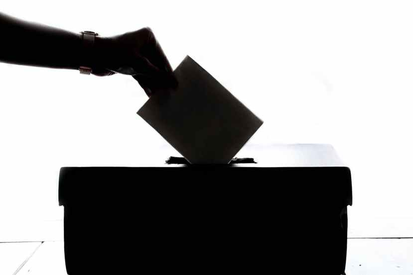 person dropping paper on box