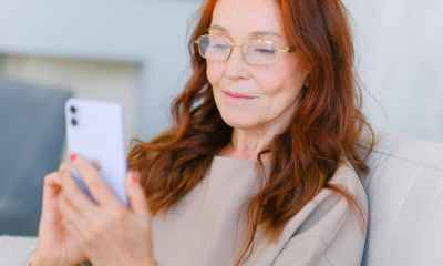 elderly woman with red hair in eyeglasses making video call