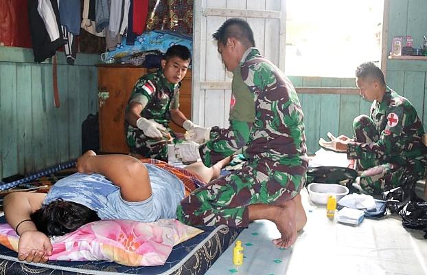 Tim kesehatan dari Yonif Raider 303/SSM saat melayani pasien orang dewasa yang baru di sunat