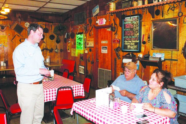 "Conner Eldridge, the Democratic candidate for U.S. Senate, visits with Jose Tijerina and Lety Hendrix at the Mount Ida Cafe. He stopped by the cafe and the courthouse as he traveled through the area on his ""Hear Arkansas's Voices"" tour.  Photo by Dewayne Holloway"