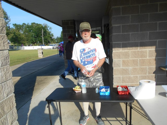 John Jack Lepkowski adds trimmings to his hamburger at the Stand Up for America Gala Saturday in the Nashville City Park. Despite temperatures in the mid-90s when gates opened, a sizeable crowd gathered in the park for the annual July 4th gala.