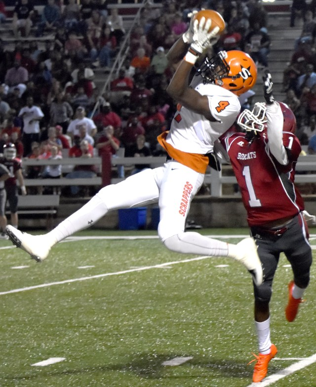 Ty Pettway (4) makes a leaping catch over Bobcat defender Charles Horton in Friday night's Scrapper victory.