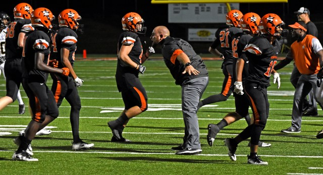 Coach Brad Chesshir congratulates his Scrapper defenders after a Robinson turnover in Nashville's 31-28 District 7-4A victory last Friday night.