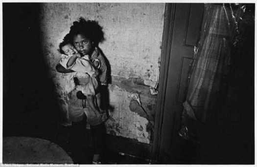 """Нервы: Молодая девушка пытается успокоить плачущего ребенка, удерживая его на груди. Пара стоять перед стеной с отслаивающимися обоями в месте, которое фотограф описывает как """"жильё ниже стандарта"""" в Balsall Хит, Бирмингем в июне 1969"""