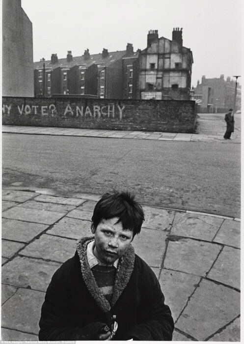 Анархия: Ник Хеджес сфотографировал лицо мальчика, живущего в бедности, который стоит в пустынной улице в Токстет, Ливерпуль в 1969 году, с грязью размазанной по его лицу.