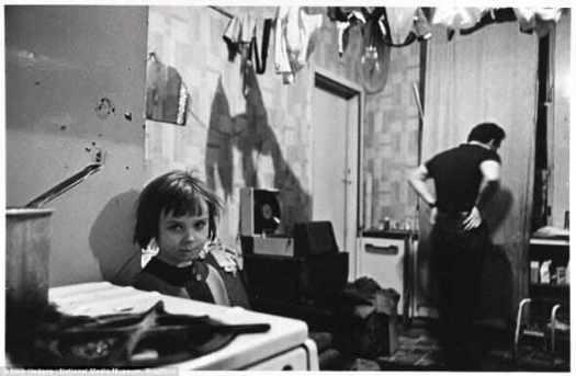 Скученность: Мистер и миссис Галлахер жили со своими четырьмя детьми на первом этаже многоквартирного квартире в Maryhill, Глазго. Их спальня в лужах дождевой воды, а ночью они спят со светом на, чтобы удержать крыс подальше — однажды ночью они насчитали 16 крыс в комнате. На фото г-н Галлахер с одним из своих детей в январе 1970.