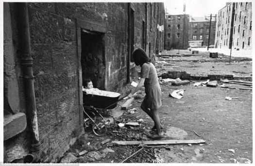 Отчаянье: Г-жа Х жила с мужем и сыном в многоквартирном блоке в Глазго, который был оставлен всеми другими семьями. Однажды утром пара проснулась, обнаружив что бригнада по сносу начали рушить их дом. На фото г-жа Х завозит своего ребенка через груды строительного мусора в холодный, неосвещенный дом.