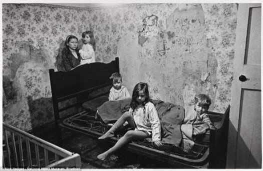 Нищета: Г-жа М ютится с ее четырьмя маленькими детьми в соцдоме, что они разделяют с мужем в Balsall Хит, Бирмингем. В их доме нет ванной, горячей водой и внутренние стены сочатся влагой. Дети спали на мокрых решётках матрсов, простеленных парой старых плащей. Они изображены в январе 1969 года, когда толстый слой снега лежал на улицах и окна были разбиты.