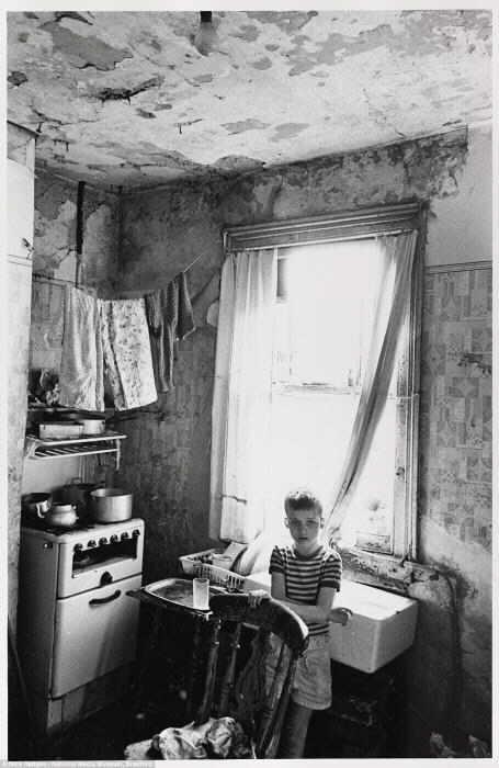 Трущобы: с плесенью и потрескавшейся штукатуркой, украшающими стены, и бельевой сушкой над плитаой, мальчик стоит один в кухне трущобного дома в Бирмингеме, Duddleston, в августе 1970 года