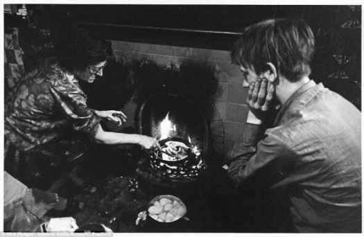 Обеденное время: Г-жа Т приседает перед очагом в доме где она живет с мужем г-н Т (на фото), Токстет, Ливерпуль.