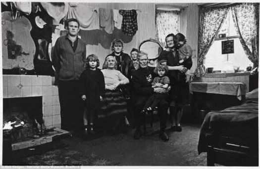 Теснта: Три поколения этой ирландской семьи, изображенные в ноябре 1969 года, жили вместе в одной комнате подвала в коммунальной квартире дома в Токстете в Ливерпуле. Члены девяти семей позируют под своим бельём, которое сушится от тепла очага на импровизированной сушильной верёвке.