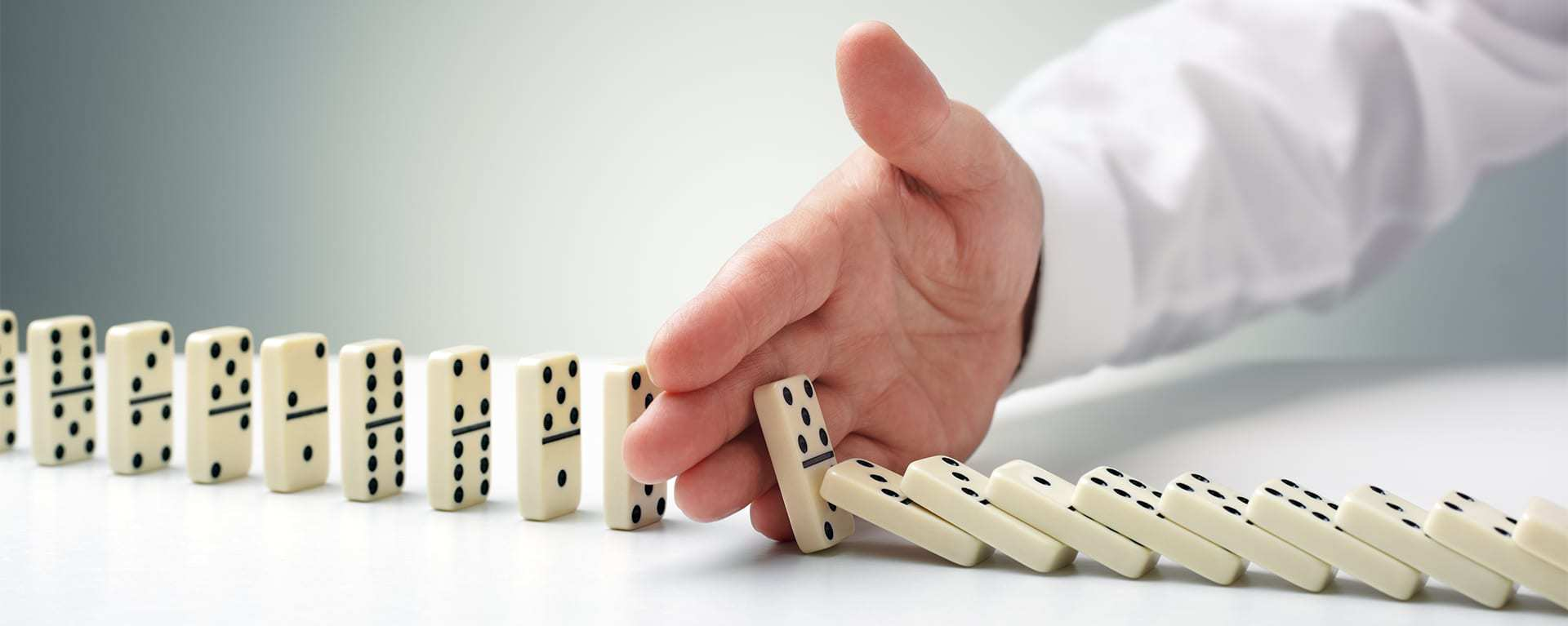 Image of falling dominos being stopped by Swartz Consulting services