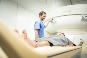 radiologist tech performing imaging scan on middle aged patient