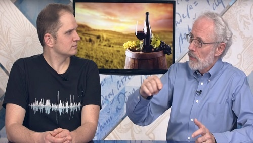 Curtis and Jonathan sit at the anchor desk, an image of a wine bottle, a wine glass, and grapes on a wine barrel behind them.
