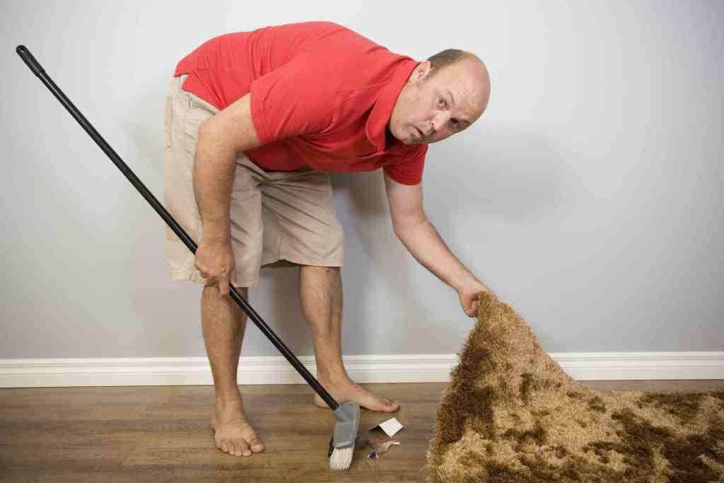 att sopa något under matten