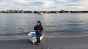 Dana with the dinghy on the island near Wrightsville Beach. Swedish Fish lies at anchor in the background.