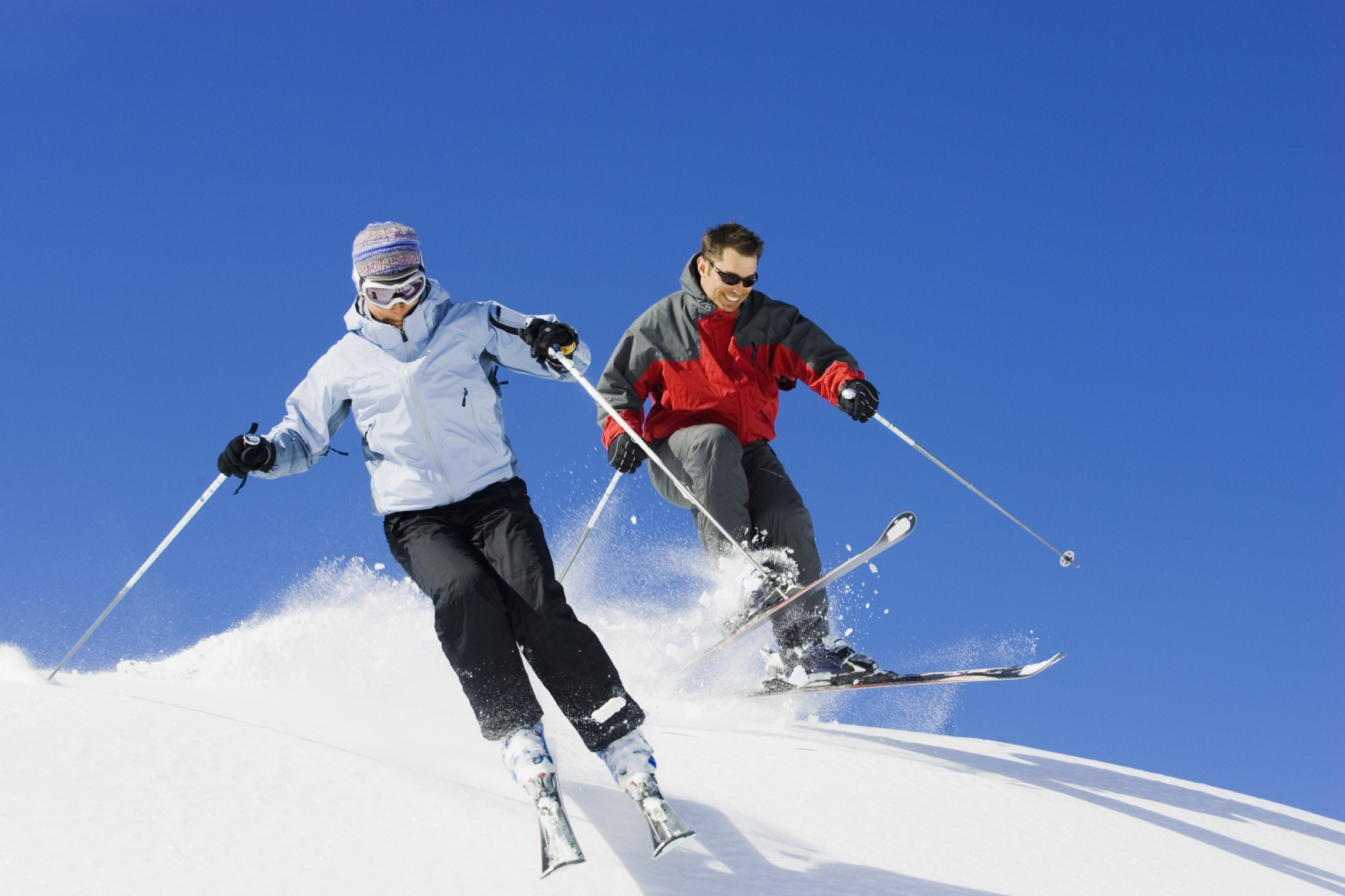 Couple downhill skiing