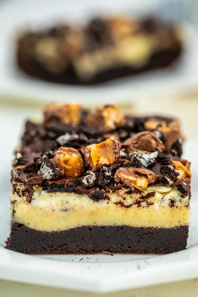 Slutty Cheesecake Brownie Bars made with a layer of fudgy brownie, Oreos, cheesecake, chocolate ganache and chopped Snickers bars. #brownies #bars #dessertrecipes #sweetandsavorymeals #chocolate