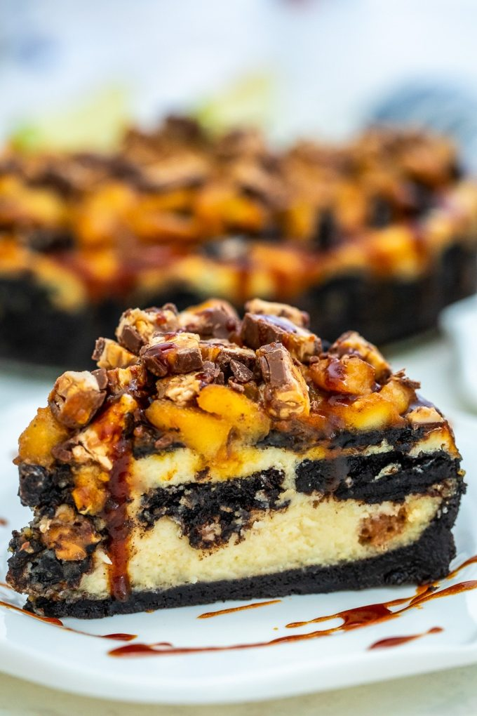 Apple Snickers Cheesecake is not your ordinary dessert! It has your favorite chocolate bar and fruit rolled into one unique and unforgettable cheesecake! #cheesecake #snickers #appledesserts #sweetandsavorymeals #halloweenrecipes