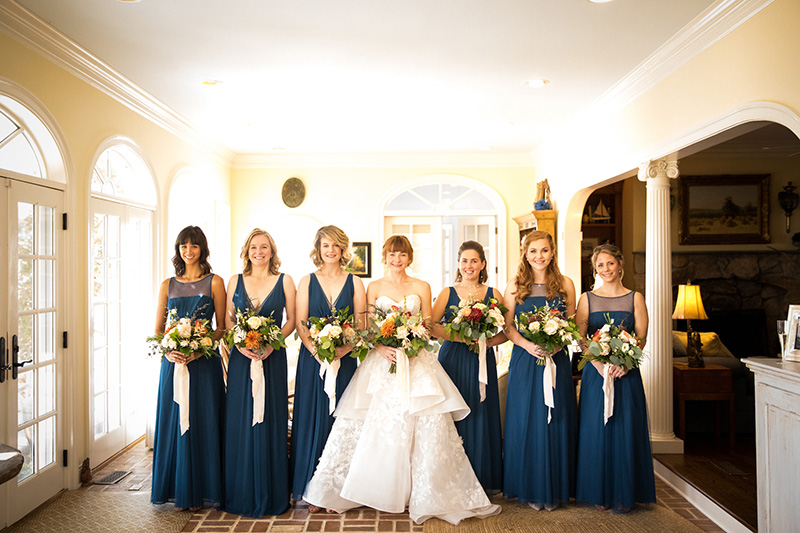 Bridesmaids in Navy Posing with orange, red and green Bridal Flowers by Sweetbay Flowers | Eastern Shore Florist|