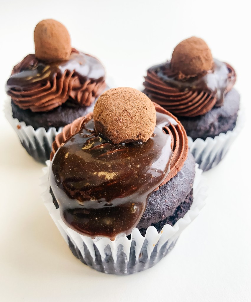 Front angle view of chocolate cupcake trio with chocolate frosting, caramel sauce, topped with chocolate truffle