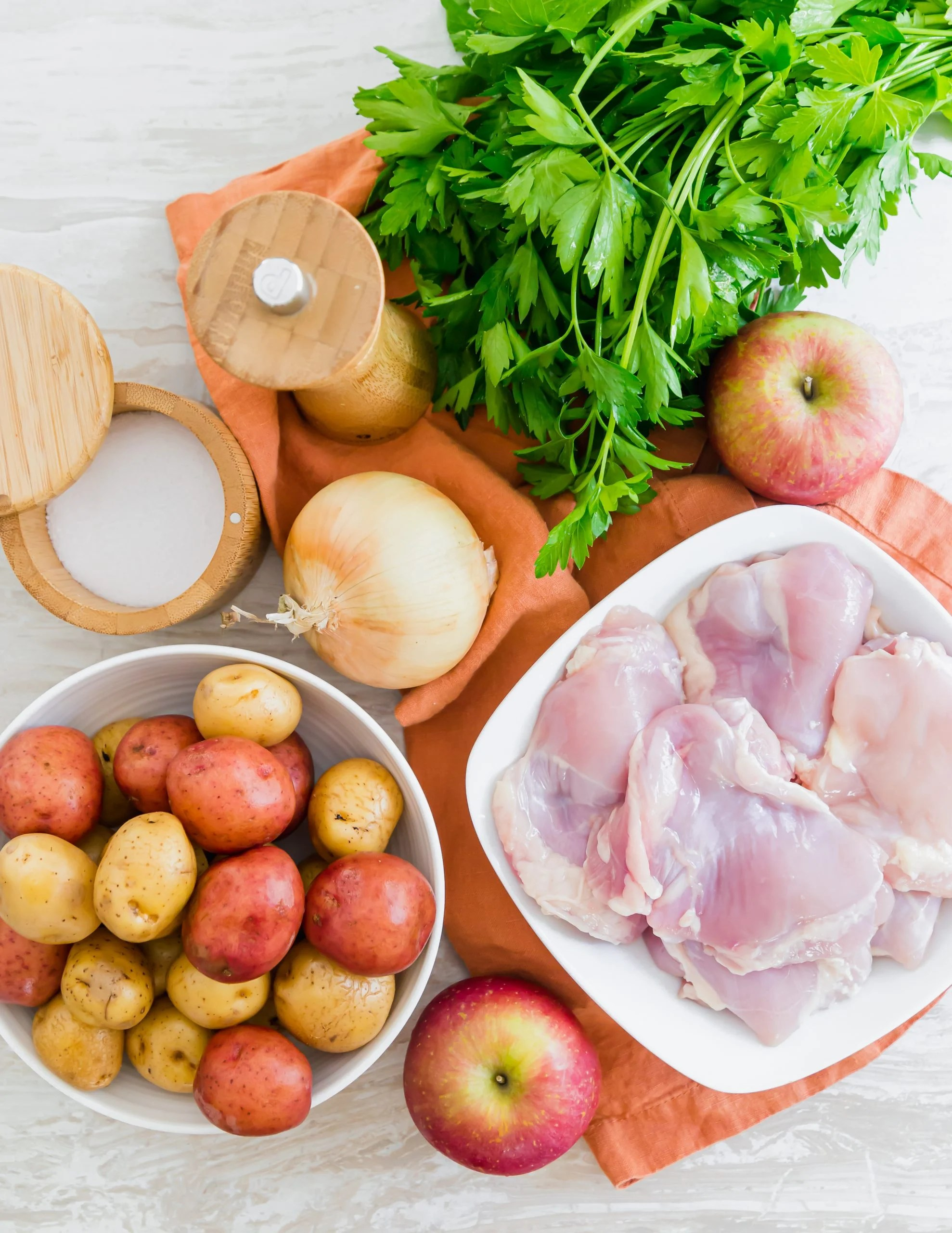picture of chicken thighs, onion, salt, pepper, parsley, potatoes, and apples on a table
