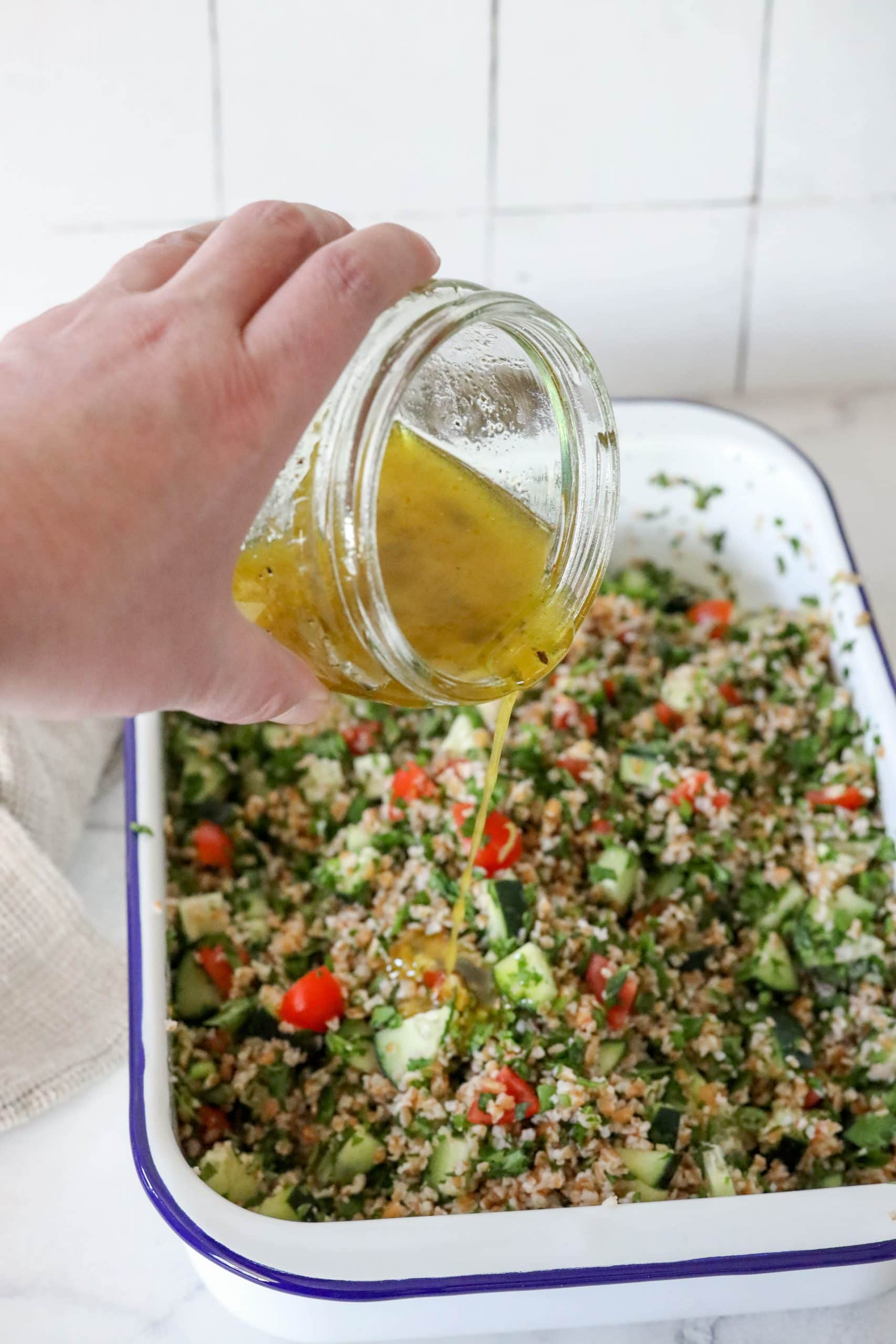 picture of hand pouring olive oil and juice over tabbouleh