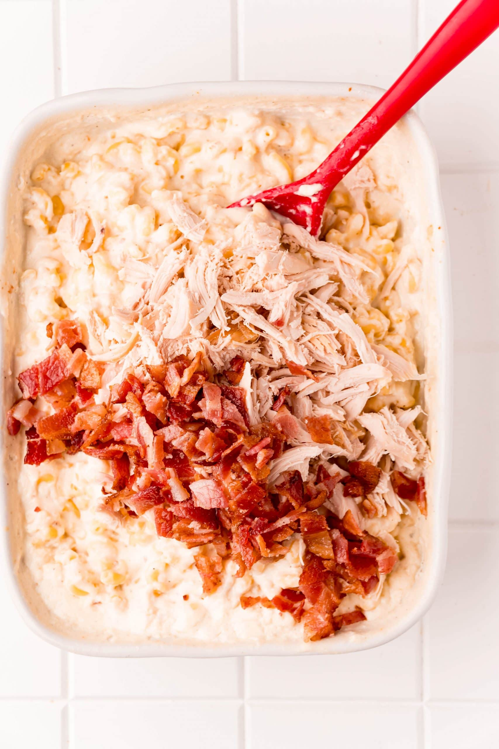 picture of chicken and bacon being stirred into creamy macaroni and cheese
