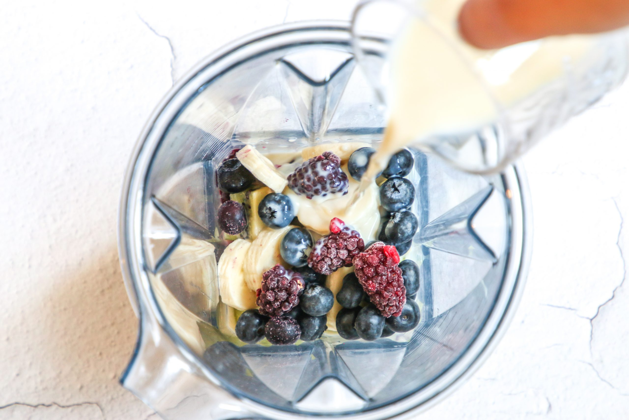 picture of banana and berries in a blender with almond milk being poured in