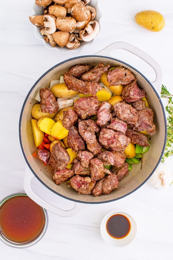 picture of browned venison meat being added to a pan