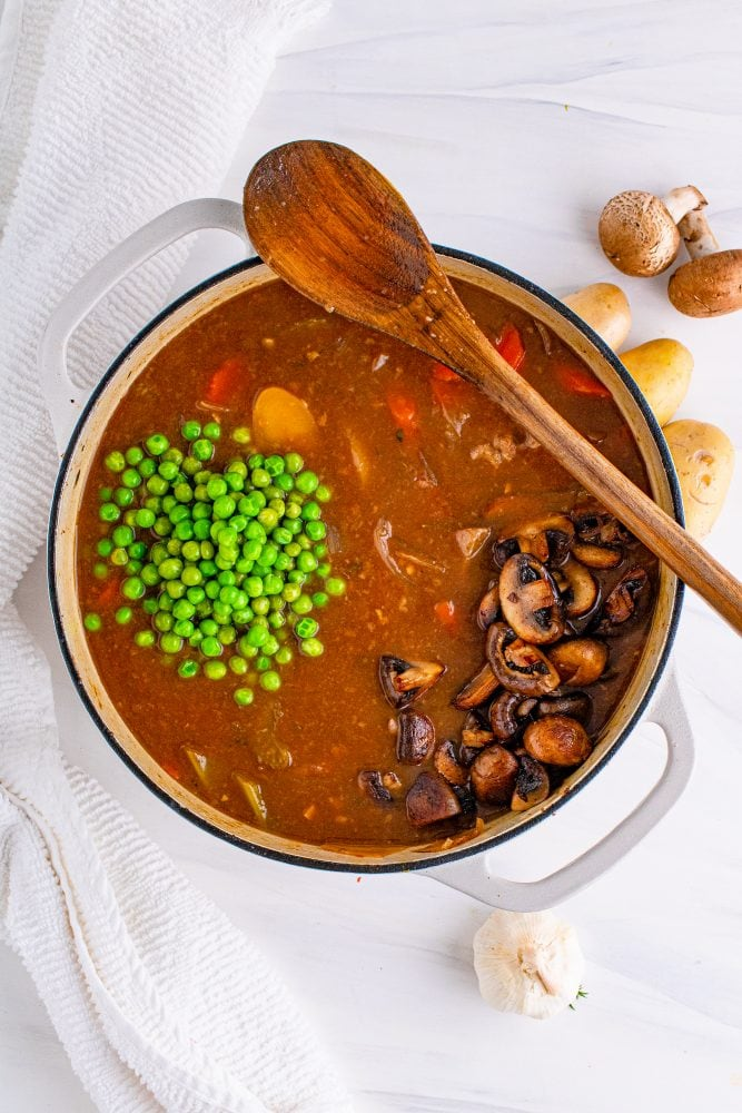 peas being added to venison stew in a pot