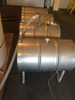 Stainless steel barrels being filled with juice to ferment into wine.