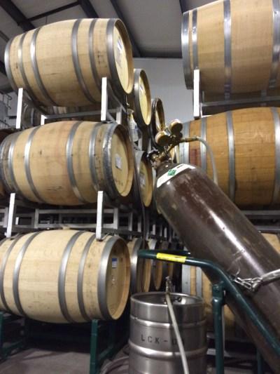 Keg of wine and nitrogen tank in front of barrels.