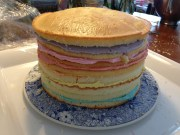 Rainbow frosting between split layers of white cake.