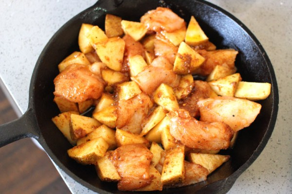 Scooping chicken and potatoes into skillet