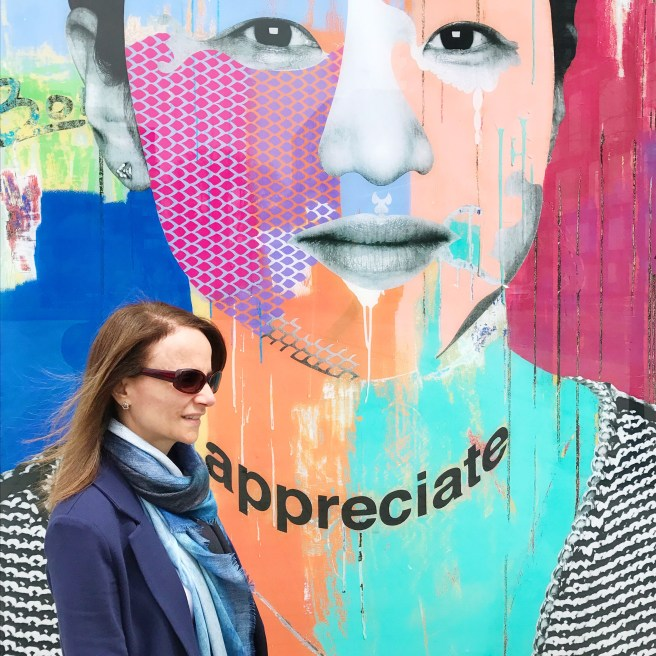 In front of one of the 12 portraits from the Faces of Regent Park, a downtown Toronto neighborhood (By Toronto artist Dan Bergeron)