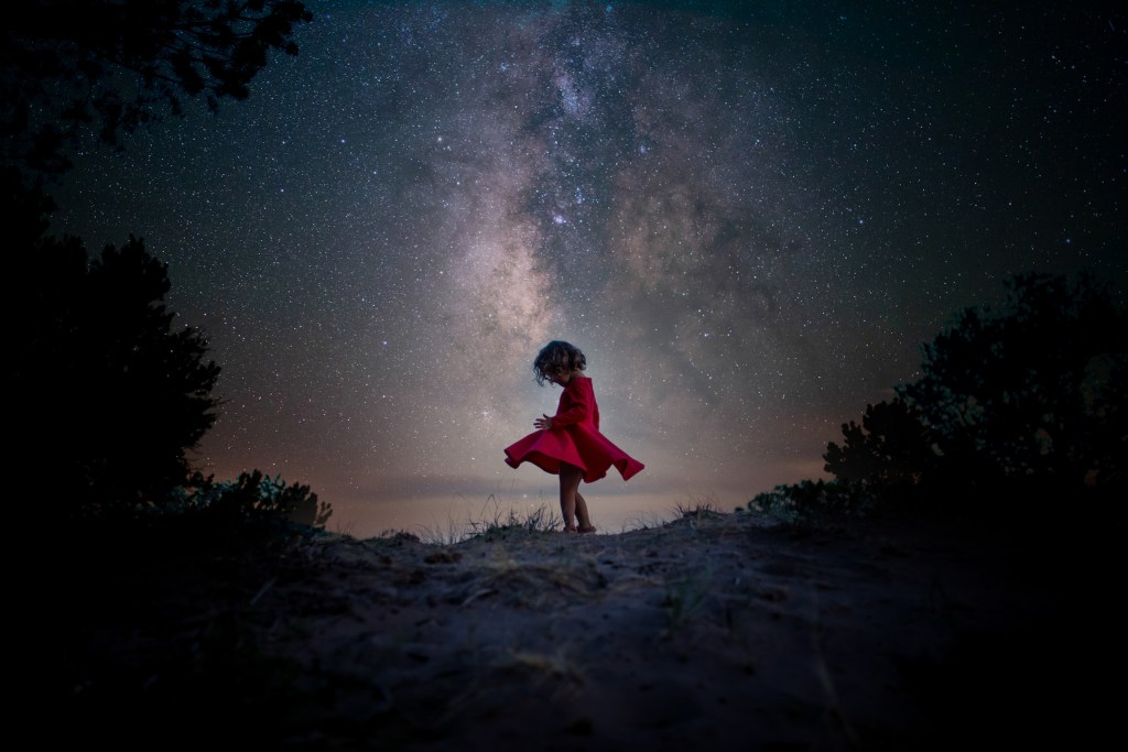 Photo of girl dancing in a red dress in front of the Milky Way