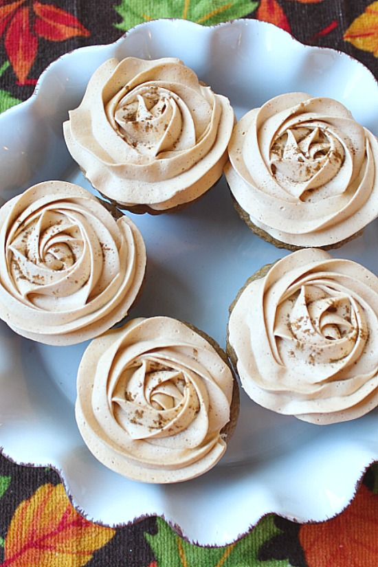 5 cupcakes topped with cool pumpkin frosting.