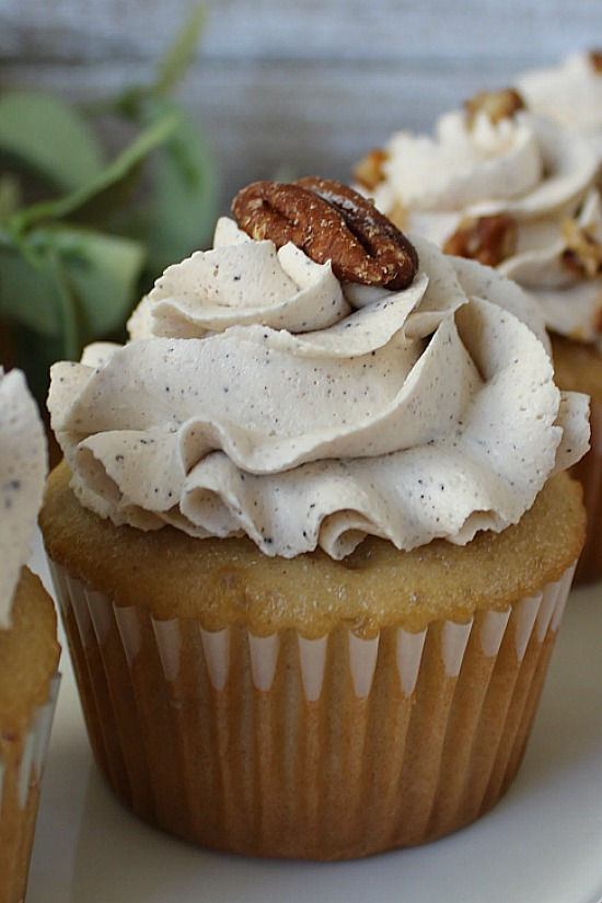 Toasted pecan half topping frosted cupcake.