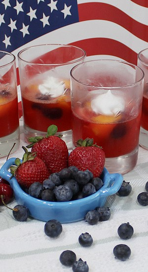 Strawberries and blueberries showcased with desserts in clear glasses.