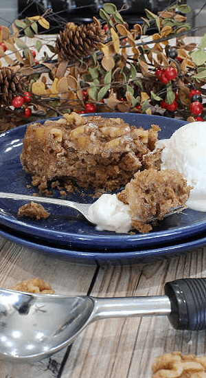 A forkful of ice cream and spice cake loaded with fresh baked apples and walnuts.