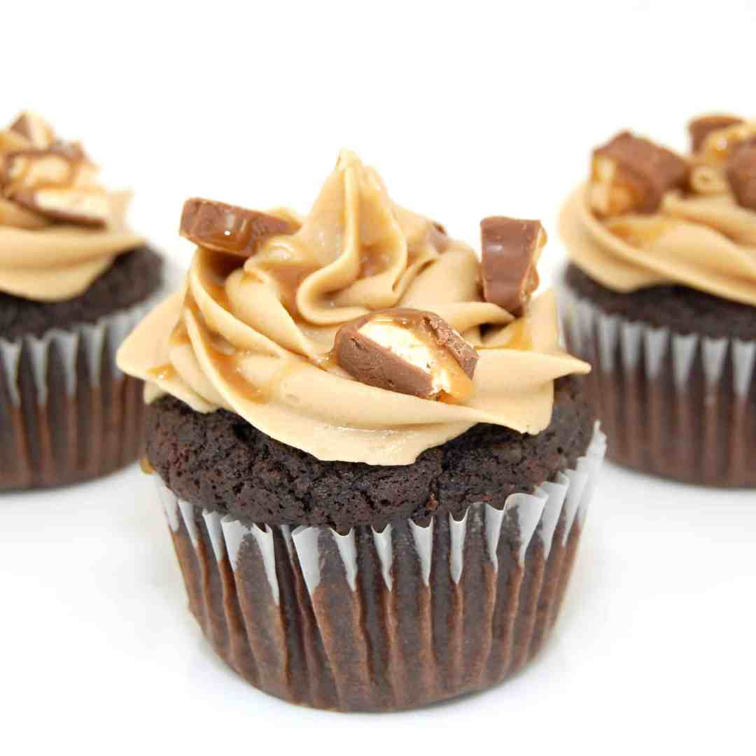 snickers cupcake with caramel frosting and Snickers on top