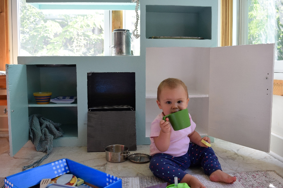 Playing with her kitchen.