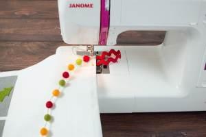 Sewing Pom Noms onto an advent calendar
