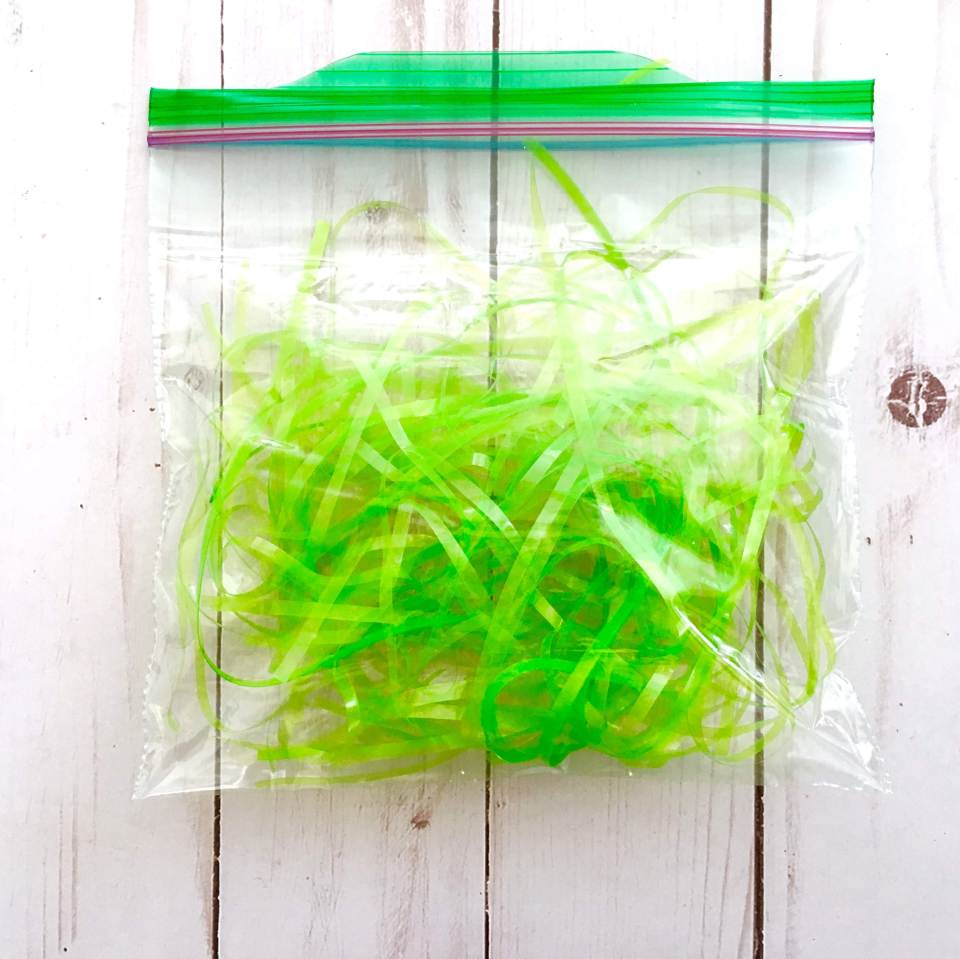 Sandwich sized zip-lock baggie filled two thirds with easter grass.