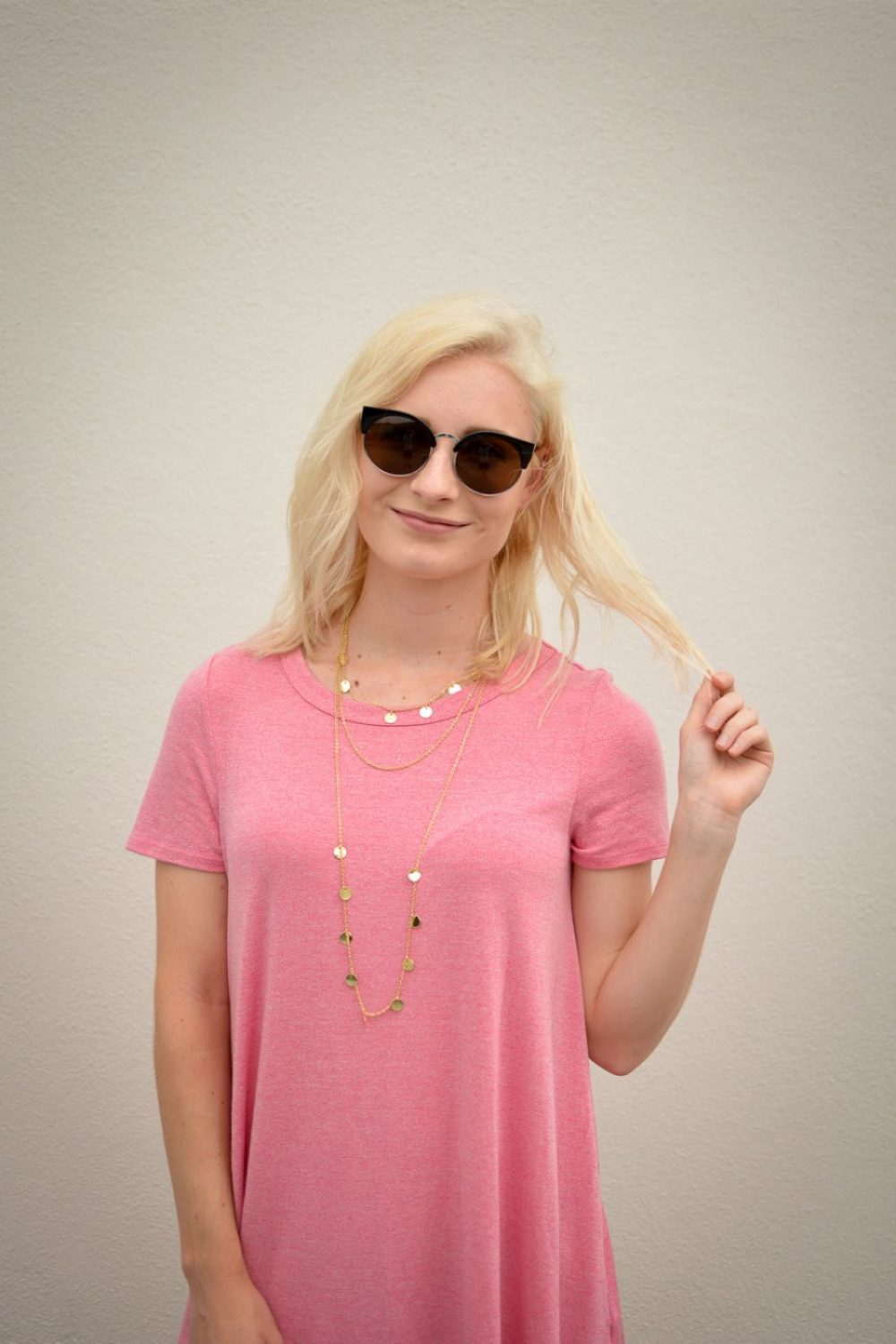 A pink t-shirt dress, come cat eye sunglasses, and lace up sandals.