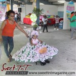 Girl in pink flower dress on wheelchair at special needs children Easter Bonnet parade at Queen's Park Cricket Club, color eggs, Sweet T&T, Sweet TnT, Trinidad and Trini,