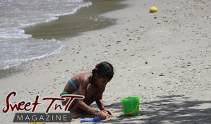 Girl on beach making sand castle with green pale and blue shovel at Chaguaramas Beach in Sweet T&T, Sweet TnT Magazine, Trinidad and Tobago, Trini, vacation, travel Chaguaramas Boardwalk