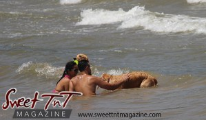 Syrian couple in sea water with two brown dogs, waves, Chaguaramas Beach in Sweet T&T, Sweet TnT Magazine, Trinidad and Tobago, Trini, vacation, travel Chaguaramas Boardwalk