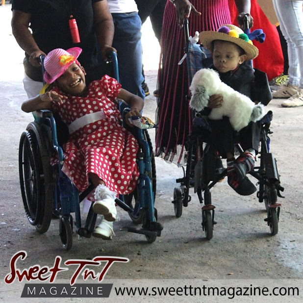 Girl in red and white polka dot dress, white belt, white shoes, and pink hat with yellow flower on wheelchair and boy with black suit, black shoes, straw hat and colored eggs holding white toy puppy on wheelchair models at special needs children Easter Bonnet parade at Queen's Park Cricket Club, color eggs, Sweet T&T, Sweet TnT, Trinidad and Tobago, Trini, vacation, travel